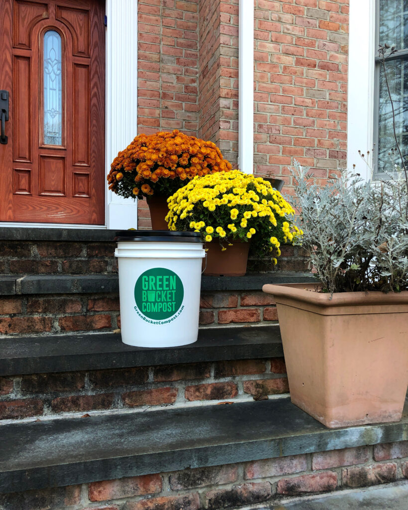 The Green Bucket Compost bucket sitting on a porch step of a residence